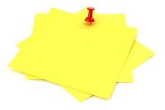 Three yellow sticky notes. Thumbtacked to white background, focus is set on thumbtack Stock Photo