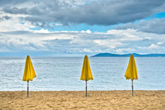 Three yellow sunshades on sandy beach against blue sky, Sithonia Stock Photos
