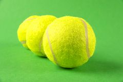 Three yellow tennis balls on green background Royalty Free Stock Photo