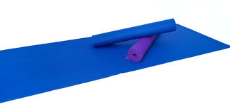 Three yoga exercise mats on white. A blue yoga exercise mat is laid out flat and ready to use with two additional mats rolled up against white Royalty Free Stock Photography