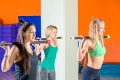 Three young active girls are engaged in the gym with a coach, li. Ft weights royalty free stock images