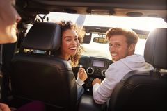 Three young adult friends in a car on a road trip together royalty free stock photo