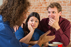 Three Young Adult Friends. Fascinated friends listening to men in cafe Stock Image