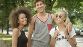 Three young adult friends having fun in a city park. Royalty Free Stock Photos