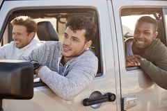 Three young adult male friends going on vacation in a car stock photo