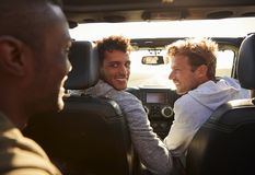 Three young adult men driving with sunroof open, back view stock photography