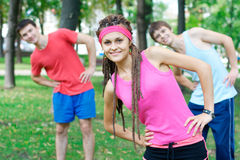 Three young adults exercising outdoors. Three young adults exercising at the park Stock Image