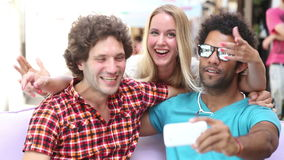 Three young adults having fun taking spontaneous selfies. Two young men and a blonde woman having fun and taking selfies in town stock video footage