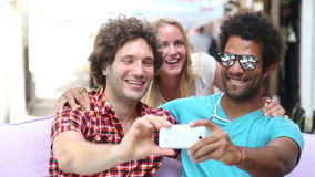 Three young adults having fun taking spontaneous selfies. Two young men and a blonde woman having fun and taking selfies in town stock video