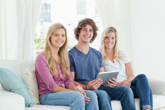 Three young adults look at the camera as they hold a tablet in t Stock Image