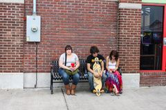 Three young adults sitting on an urban bench Tulsa Oklahoma USA circa May 2010 Royalty Free Stock Photography