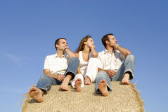 Three young adults on a straw bale Royalty Free Stock Image