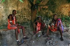 Three young Africans, Masai clothing, rest in the shade. Stock Image