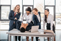 Three young angry businesswomen punishing businessman lying on table Stock Photography