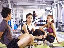 Asian young man and women resting during exercise. Three young asian adults, male and female, sitting on floor resting relaxing talking during workout Stock Images