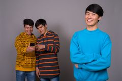 Three young Asian friends together against gray background royalty free stock image