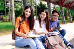Three young Asian people studying together at outdoors. Education and Technology concept. Lifestyles and Happy life in classroom stock photography