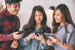 Asian people using and looking at mobile phone and tablet pc together stock photo