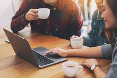 Asian people using and looking at the same laptop computer during a meeting royalty free stock image