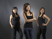 Three Young Asian Teens posing with confidence. Three Beautiful Young Asian Women Dressed Casually In Black Tops Stock Images