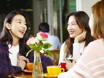 Three young asian women chatting talking in coffee shop. Three happy beautiful young asian women sitting at table chatting talking in coffee shop or tea house royalty free stock photos