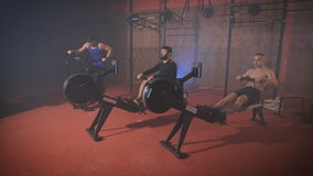 Three young athletes doing exercises on training apparatus. Three young athletes doing exercises on training apparatus at the same time. Athletes in the gym stock footage