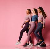 Three young athletic girls in high-tech modern colorful sportswear vigorously walk together towards free text space on pink royalty free stock photography