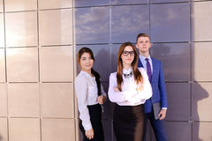 Three young attractive educated young businessman smiling, holdi Royalty Free Stock Photo