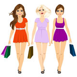 Three young attractive smiling girls in summer mini dresses walking and holding shopping bags Royalty Free Stock Images