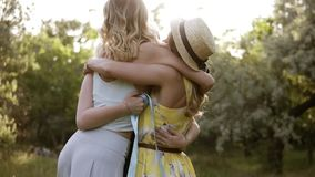Three young, attractive women hugging each other. Loving friends. Friendship meeting. Slow motion.  stock footage