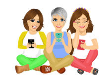 Three young attractive women sitting on floor using their smartphones smiling happy. Over white background Royalty Free Stock Image