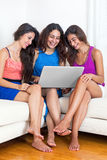 Three young barefoot girlfriends sitting on sofa with laptop, la Royalty Free Stock Image
