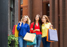 Three young beautiful female friends walking with shopping bags Stock Photos