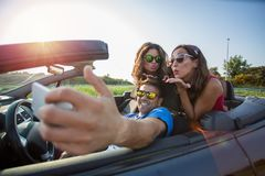 Three young beautiful friends taking a selfie picture in a convertible car stock image