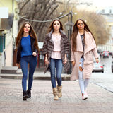 Three young beautiful girlfriends in autumn clothes walking on t Royalty Free Stock Photography