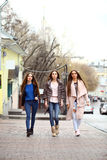 Three young beautiful girlfriends in autumn clothes walking on t Stock Photos
