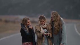 Three young beautiful girlfriends traveler watching photos from the camera outdoors, on the road, laughing. Blonde friends view ph stock video