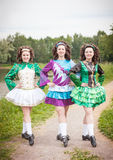 Three young beautiful girls in irish dance dress posing outdoor Stock Photos