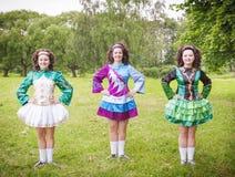 Three young beautiful girls in irish dance dress posing outdoor Stock Photo