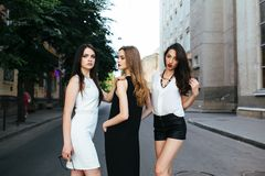 Three young beautiful girls posing in the street Royalty Free Stock Photos