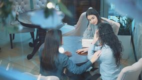 Three young beautiful girls are sitting in a cafe. During this girlfriend communicate. Have nice black long hair. After. A long separation. Slow video stock footage