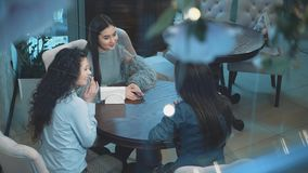 Three young beautiful girls are sitting in a cafe. During this girlfriend communicate. Have nice black long hair. After. A long separation. Slow video stock video