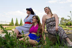 Three Young beautiful plus size models are sitting on rock. Three Young beautiful plus size models are sitting on a rock , xxl women portrait near the lake Stock Photo