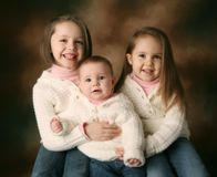 Three young beautiful sisters. Studio portrait of three cute young sisters hugging each other wearing white cream sweaters on a brown background, baby, toddler Royalty Free Stock Photography