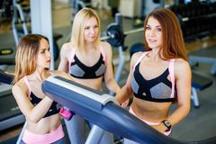 Three young beautiful smiling woman talking in the gym Royalty Free Stock Photography