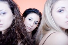 Three young beautiful women. Young women posing against orange background; focus on the brunette from the center Royalty Free Stock Photos