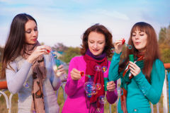Three young beautiful women blow bubbles Stock Photos