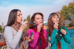 Three young beautiful women blow bubbles Royalty Free Stock Photos