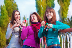 Three young beautiful women blow bubbles Royalty Free Stock Photo