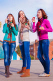 Three young beautiful women blow bubbles Royalty Free Stock Images